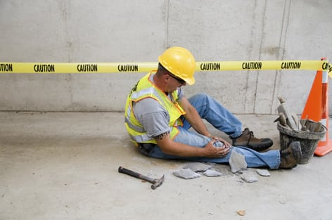 injured construction worker holding knee