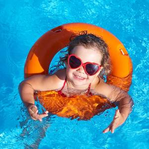 little girl swimming in pool with float and sunglasses
