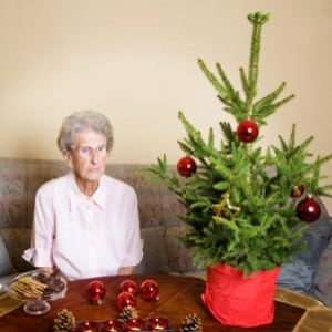 Elderly woman sitting next to Christmas tree