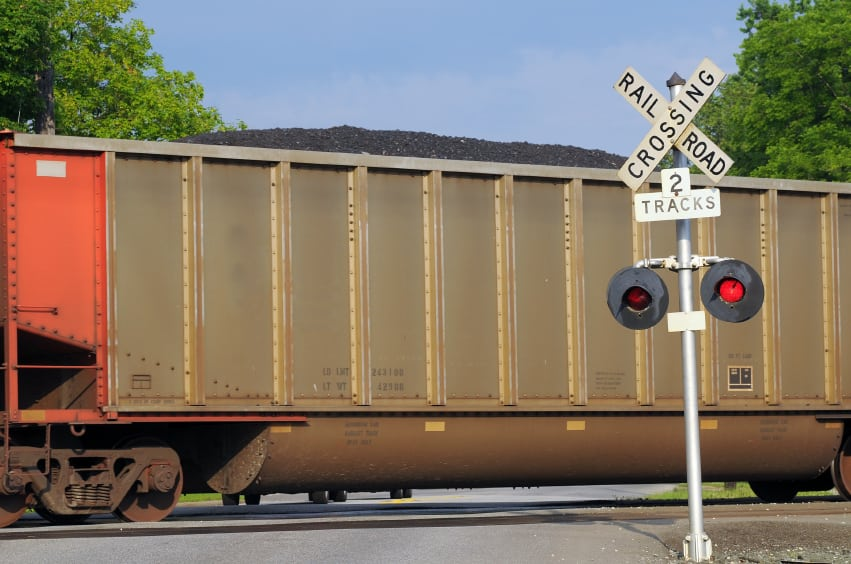 Freight car filled with coal passes over a grade crossing with warning signal